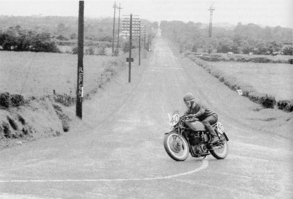 Arthur Wheeler at the end of Dundrod's straight on a works DOHC 250 in 1952, note the enormous 8 gallon aluminium tank, held on with a third tube from the top of the steering head to the top of the seat tube, passing straight through the centre of the tank. Also of note is the lack of friction dampers on the lower arms connecting the fork yoke to the girders. These forks were apparently especially shortened to cope with the lower steering head position and the use of a 19 inch front wheel. Although I have never laid eyes on such they are said to have needle roller spindles and a hydraulic damping unit, and the bikes handled superbly.