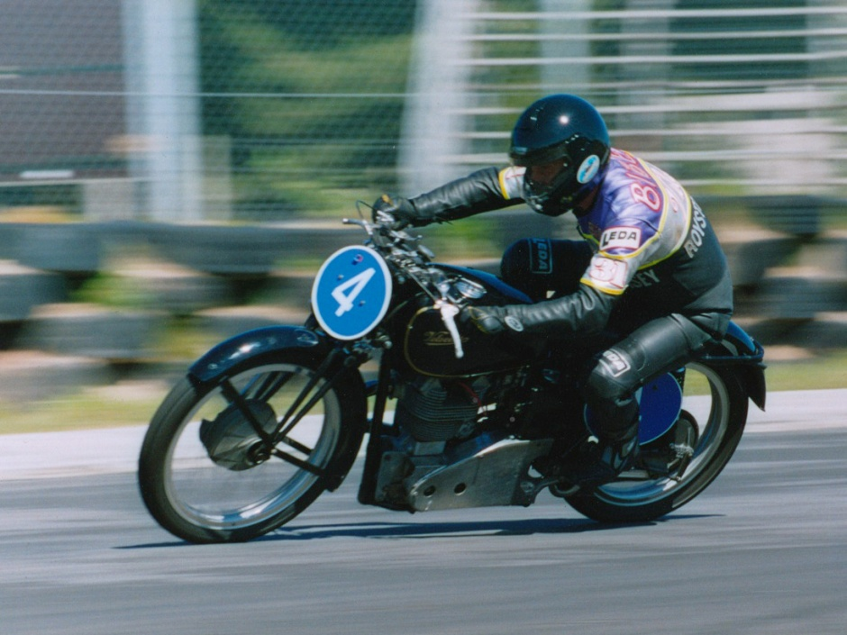 Feature image: 'Local' man Bill Biber in resplendent purple and silver LEDA leathers, touting his sponsor 'Royston Vasey'. This shot is from the second Burt Munro challenge where he left the girder fork class in no doubt that a Velocette is faster.